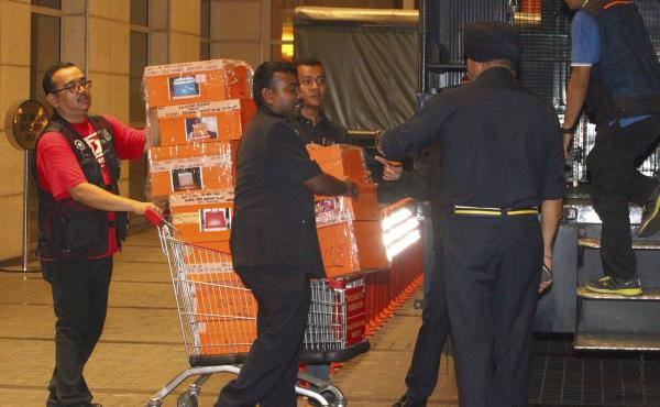 Police prepare to load confiscated items into a truck in Kuala Lumpur, Malaysia on Friday after a raid on a condominium belonging to former Prime Minister Najib Razak.