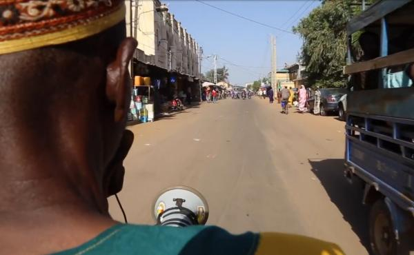 A town crier rides his moped through the city of Kayes in Mali, using his megaphone to warn people about Ebola.