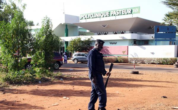 A police officer stands in front of the Pasteur clinic in Bamako, which was quarantined after a nurse there died from Ebola.