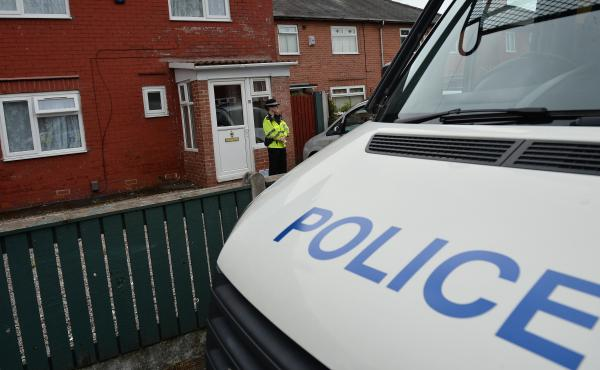 A police officer stands on duty outside a residential property in Fallowfield, in southern Manchester, on Wednesday as investigations continue into the bombing at the Manchester Arena.