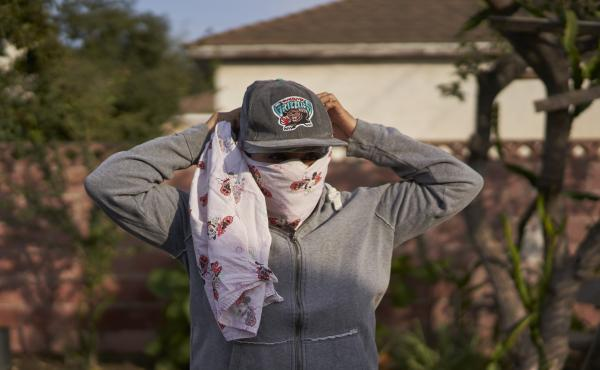Gabriela, 32, a strawberry picker from Oaxaca, Mexico, who lives in Oxnard, Calif., had to wear a bandanna to cover her nose and mouth to avoid inhaling smoke from a wildfire while working in the fields.