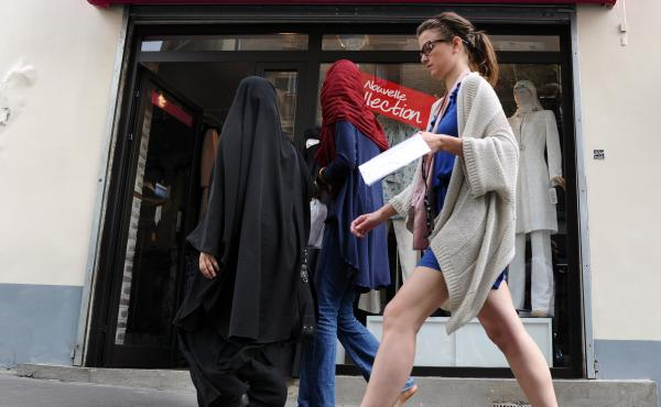 Three women, two of them partially veiled, walk past a hijabs shop in Paris. The wearing of the veil has been a serious point of contention in France, with the government banning its use in public schools and the wearing of face-covering garments, includi