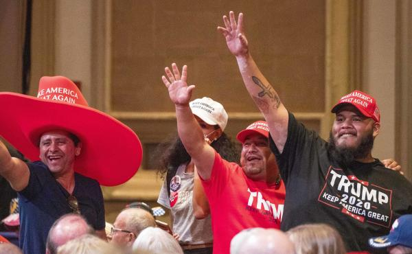 Supporters of President Trump wave during a Latinos for Trump roundtable last month at the Arizona Grand Resort in Phoenix.