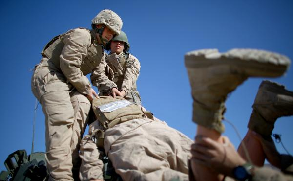 "Marine Lance Cpls. Julia Carroll (left) and Paula Pineda lift ""Carl"" — a 220-pound test dummy — during training in March in California. Female Marines have completed months of training and are now waiting to hear whether they will be allowed to serve"