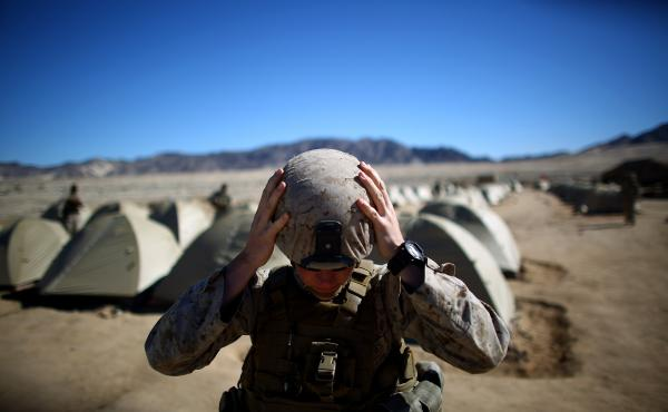 Sgt. Kelly Brown adjusts her helmet before a weapons check last year at the Marine Base at Twentynine Palms in the Mojave Desert, Calif. The Marine Corps set up a months-long training exercise to determine whether women could serve in ground combat jobs l