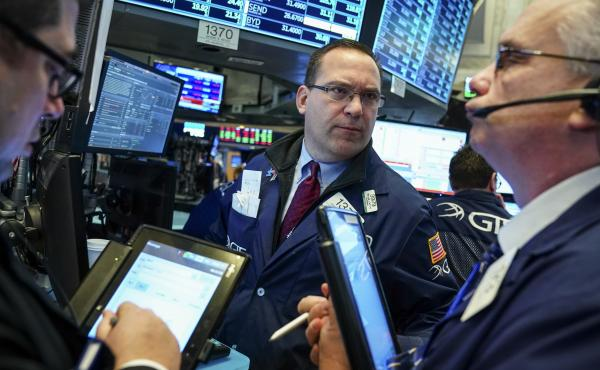 Traders and financial professionals work on the floor of the New York Stock Exchange ahead of the opening bell. Investors' worries about a trade war increased Wednesday after China announced plans to retaliate against U.S. tariffs.