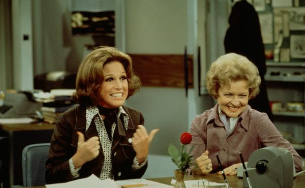 Mary Tyler Moore (left, as Mary Richards) gives a 'thumbs up' sign as she sits at her desk with Betty White (as Sue Ann Nivens) in a scene from 'The Mary Tyler Moore Show' in 1975.