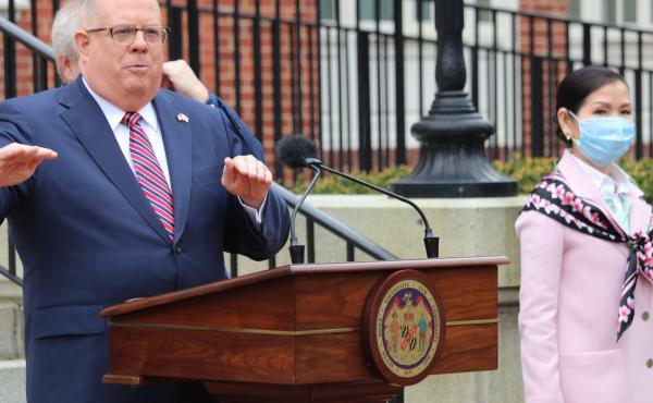 Maryland Gov. Larry Hogan speaks at a news conference on Monday in Annapolis, Md., with his wife, Yumi Hogan (right), where the governor announced Maryland has received a shipment from a South Korean company to boost the state's ability to conduct tests f
