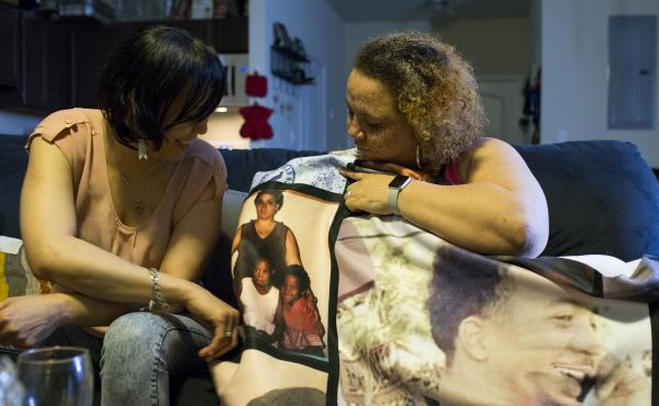 (Left) Stacy, and sister Tracy reminisce over a collage of photos of Maleak Coffin, who died three days after being shot in December. The blanket was gifted to the family by Maleak's girlfriend, Marshay Walker.
