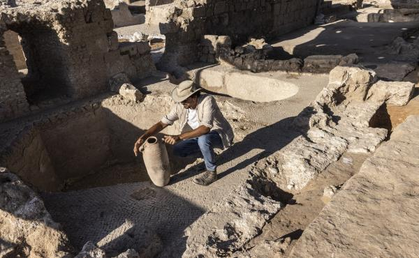 Avshalom Davidesko, from the Israel's Antiquities Authority, examines a jar in a massive ancient winemaking complex dating back some 1,500 years in Yavne, south of Tel Aviv, Israel.