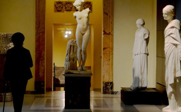 A picture taken on Tuesday shows a visitor walking past an ancient Roman marble statue at Rome's Capitoline Museum.