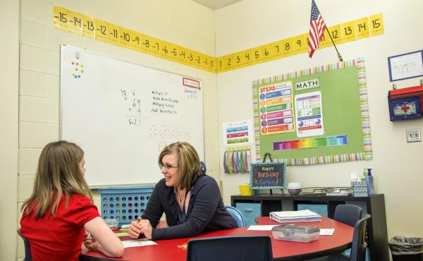 Stephanie Johnson works with a student at the Renaissance Academy, a charter school in Lehi, Utah.