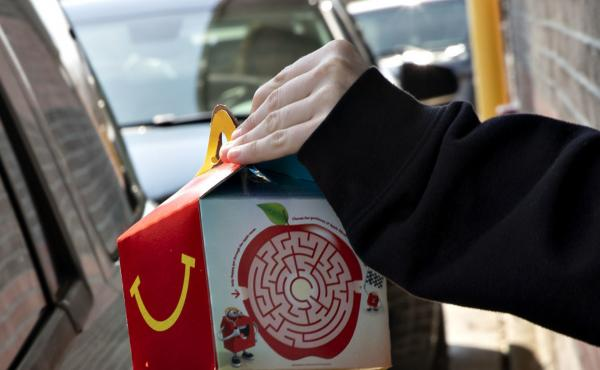 McDonald's says it will phase out most plastic from its Happy Meals by 2025. Here, a customer picks up a kid's meal at a McDonald's drive-through.