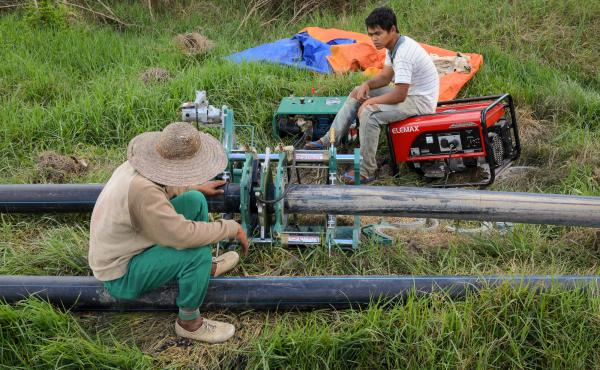 Workers with Ceria wait for a pipe-welding machine to finish connecting two sections of plastic irrigation pipe in Bario, Malaysia. The company has brought mechanized farming to the Kelabit Highlands.