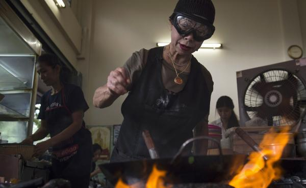 Chef Jay Fai wears a wool cap and safety goggles to ward off the heat from the charcoal fires in the alley where she cooks all of the restaurant's meals. She is such a perfectionist that she doesn't let anyone on her staff do the cooking.