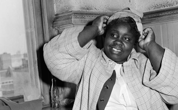 """Georgia Gilmore adjusts her hat for photographers in 1956 during the bus boycott trial of Rev. Martin Luther King Jr. in Montgomery, Ala. She testified: """"When you pay your fare and they count the money, they don't know the Negro money from white money."""""""