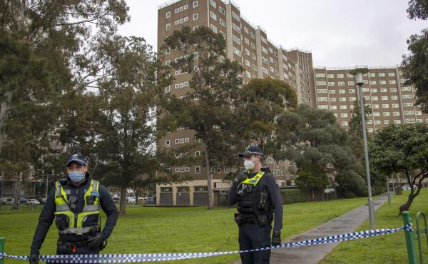 Police guard access to housing commission apartments under lockdown in Melbourne, Australia. The hard-hit Australian state of Victoria recorded two deaths and its highest-ever daily increase in coronavirus cases on Monday as authorities prepare to close i