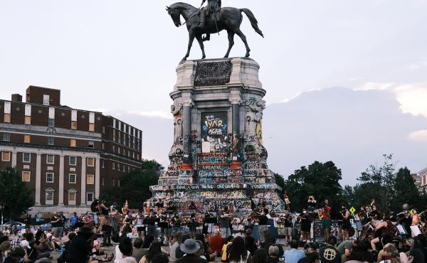 Hundreds of people gather at the Robert E. Lee monument in Richmond, Va., in July. The Mellon Foundation says it will spend $250 million over five years to re-imagine commemorative spaces in the U.S.
