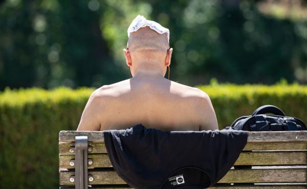 On Wednesday, a man sits shirtless on a bench along the banks of the Spree River in Berlin to keep cool.