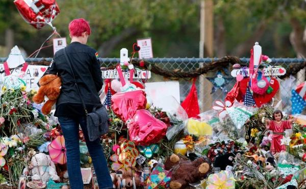 A student stops to look at a memorial at Marjory Stoneman Douglas High School in Parkland, Fla., on Feb. 28. Last month's shooting raised questions about whether states are doing enough to fund mental health services in schools.