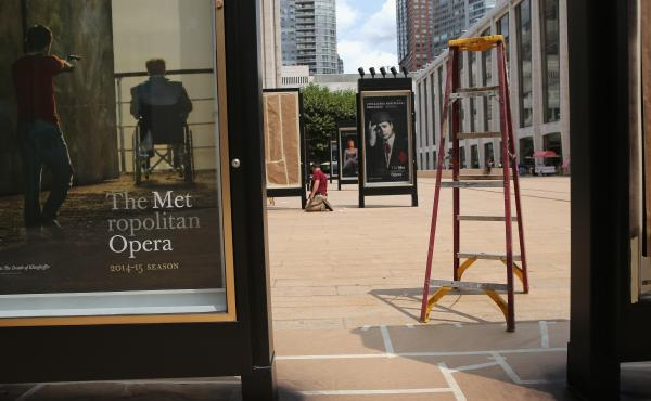 A worker unveils advertisement for future productions at the Metropolitan Opera at Lincoln Center in New York City. The Metropolitan Opera's general manager Peter Gelb has threatened a lockout if there is no an agreement with unions to that represent musi