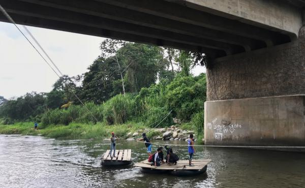 Migrants and day laborers cross the Suchiate River, which divides Mexico and Guatemala. The crossing happens despite immigration officials working on the bridge above.