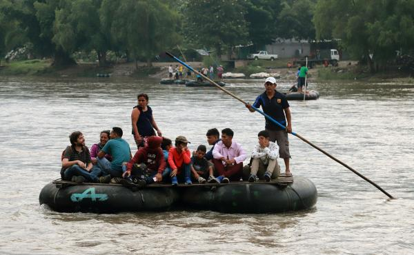 Central American migrants and a Spanish journalist ride a makeshift raft across the Suchiate River from Tecún Umán in Guatemala to Ciudad Hidalgo in Chiapas state, Mexico, on June 11.