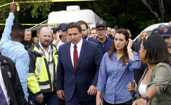 Florida Gov. Ron DeSantis (center) and Lt. Gov. Jeanette Nuñez (center right) arrive for a news conference near where a section of a 12-story beachfront condo building collapsed on Thursday in the town of Surfside.