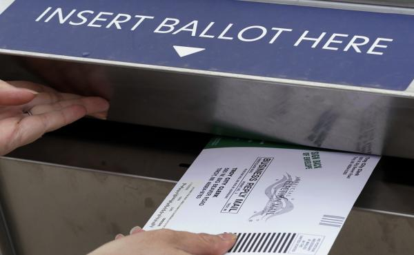 A voter is shown inserting her absentee voter ballot into a drop box earlier this month in Troy, Mich. A Michigan judge has blocked a ban on openly carrying guns in polling places on Election Day.