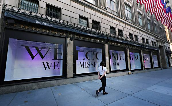 A pedestrian walks by Saks Fifth Avenue as New York City continues relaxing more restrictions imposed to curb the coronavirus pandemic.