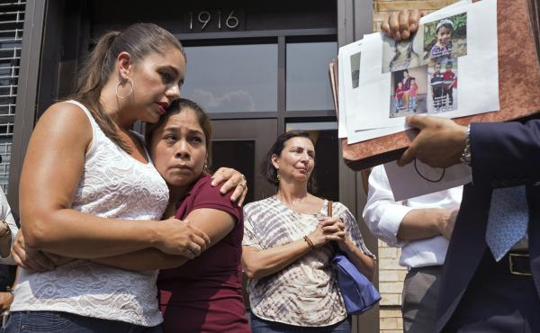Yeni Gonzalez (center), a Guatemalan mother who was separated from her three children at the U.S.-Mexico border, is embraced by volunteer Janey Pearl Starks as pictures of other children separated from their families are displayed during a news conference