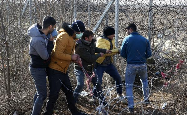 Migrants try to cut the fence at the Turkish-Greek border near the Pazarkule border gate in Edirne, Turkey, on Monday. Thousands of migrants and refugees massed at Turkey's western frontier, trying to enter Greece by land and sea after Turkey said its bor