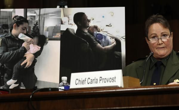 U.S. Border Patrol Chief Carla Provost testifies by a photo of agents with children during a Senate Judiciary Border Security and Immigration Subcommittee hearing.