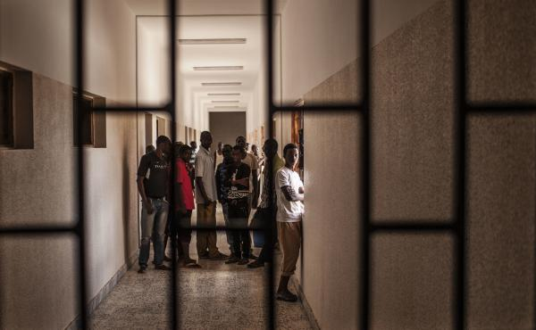 Detainees stand in a hall at a detention center for migrants in Al Kararim, Libya. The North African country is a key transit spot and destination for migrants seeking employment or a path to Europe.