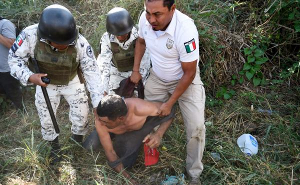 Members of the Mexican National Guard and officers of the Migration Institute detain a Central American migrant heading in a caravan to the U.S. in Ciudad Hidalgo, Chiapas State, Mexico, on Jan. 23.