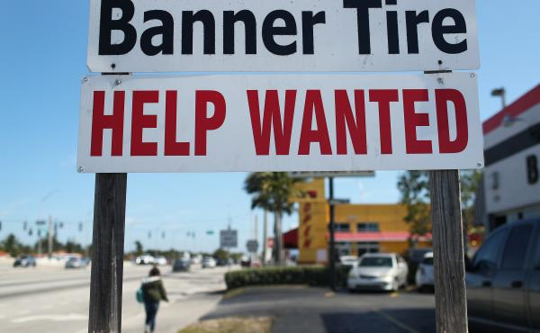 "A ""Help Wanted"" sign is posted in front of a business on Feb. 4 in Miami. Although millions are unemployed, some businesses that require being on-site are struggling to find workers."