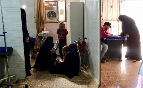 Women sit on the floor as they wait in a clinic at the al-Hol detention camp.