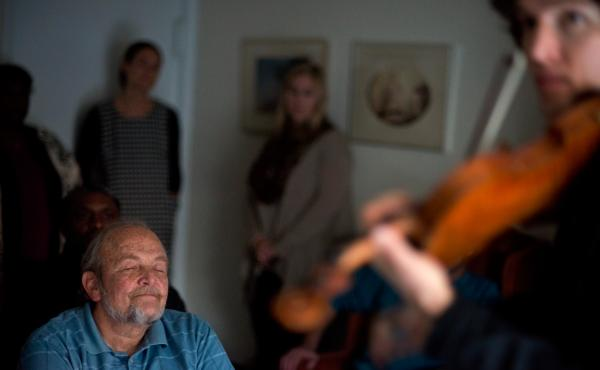 Wall (left) listens to violinist  Fain perform during the Make Room concert at Wall's apartment in Annapolis, Md. The concert is a fundraiser to help Wall pay his rent and shine a light on the growing lack of affordable housing.