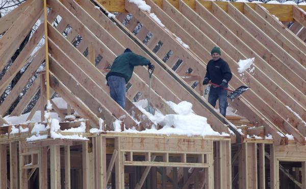 Men shovel snow off the top of a building under construction in Franklin Lakes, N.J., on Thursday. Job growth in February was led by a sharp increase in construction employment.
