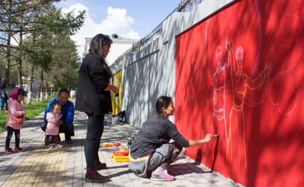 "They're the only two female artists working on a Mongolian street mural about the U.N. Sustainable Development Goals: Michid Enkhbat (stooping) and Odno Bold. The goal they're illustrating: ""gender equality."""