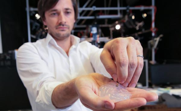 Gregoire Courtine, a neurologist at the Swiss Federal Institute of Technology, holds a silicone model of a primate's brain with an electrode array. The goal is to pick up signals from the brain and transmit them to the legs.