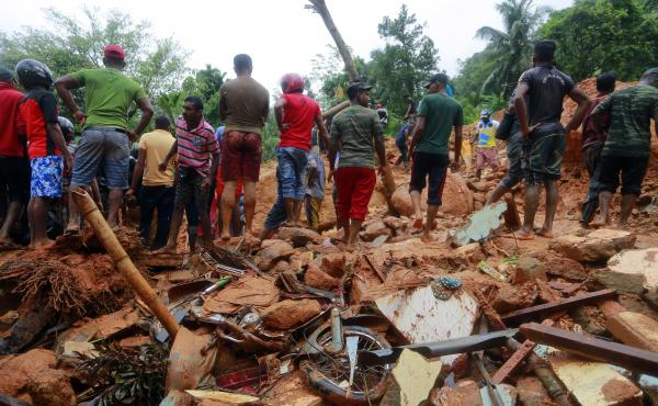 Sri Lankan military rescuers and villagers stand on the debris of a house that was destroyed in a landslide in the village of Bellana, in the Kalutara district of Sri Lanka, on Friday. Mudslides and floods triggered by heavy monsoon rains have killed scor