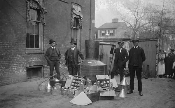 Onlookers watch as suited men stand in front of a large copper kettle still for making illegal liquor, with boxes of bottles and funnels spread before them all for the manufacture of booze, circa 1900.