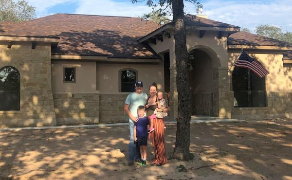 Caroline Wells and her family at their new home outside San Antonio. The builders just finished it so the yard has yet to be planted, but the couple are looking forward to letting the kids run out their energy with a lot more outdoor space than they had a