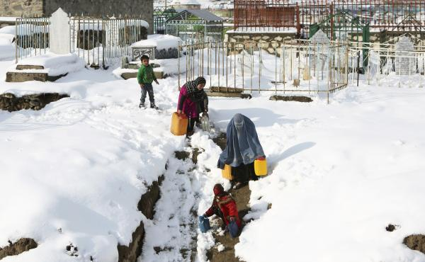 A woman and her children carry containers of water on the outskirts of Kabul, Afghanistan, on Monday. Avalanches have killed more than 100 people in Afghanistan and Pakistan.