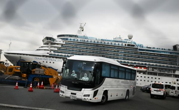 A bus departs from the dock where the Diamond Princess cruise ship sits under quarantine with its thousands of passengers and crew. Japanese authorities said Friday that some older passengers who tested negative for the coronavirus were allowed to disemba