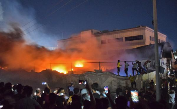 People gather as a massive fire engulfs the coronavirus isolation ward of al-Hussein hospital in the southern Iraqi city of Nasiriyah, late on Monday.