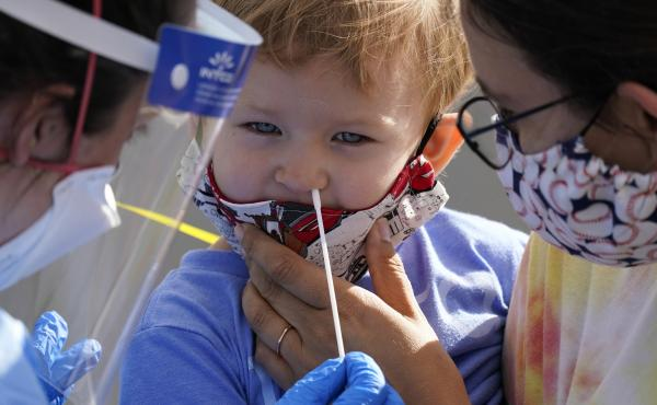 Penny Brown, 2, is held by her mother, Heather Brown, as her nose is lightly swabbed during a test for the coronavirus in Seattle last month. A survey of state health department website data shows severe illness and death among children with COVID-19 is r