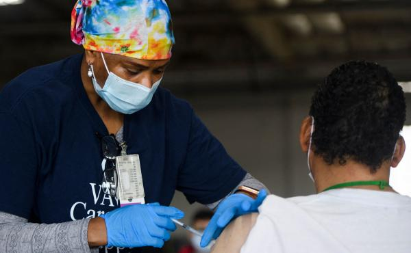 A nurse administers the Moderna COVID-19 vaccine at a Veterans Administration Long Beach Healthcare System pop-up vaccination site at the Dae Hueng Presbyterian Church on Saturday in Gardena, Calif. More than half of U.S. adults have now received at least