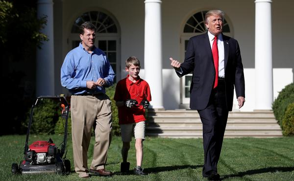 """Eleven-year-old Frank """"FX"""" Giaccio walks with President Donald Trump while mowing the grass in the Rose Garden of the White House on Friday. Also pictured is Frank's father, Greg Giaccio."""